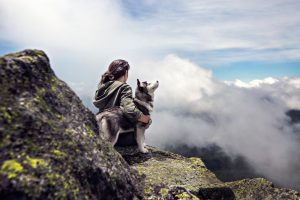Woman with her rescue dog on top of a mountain above the clouds